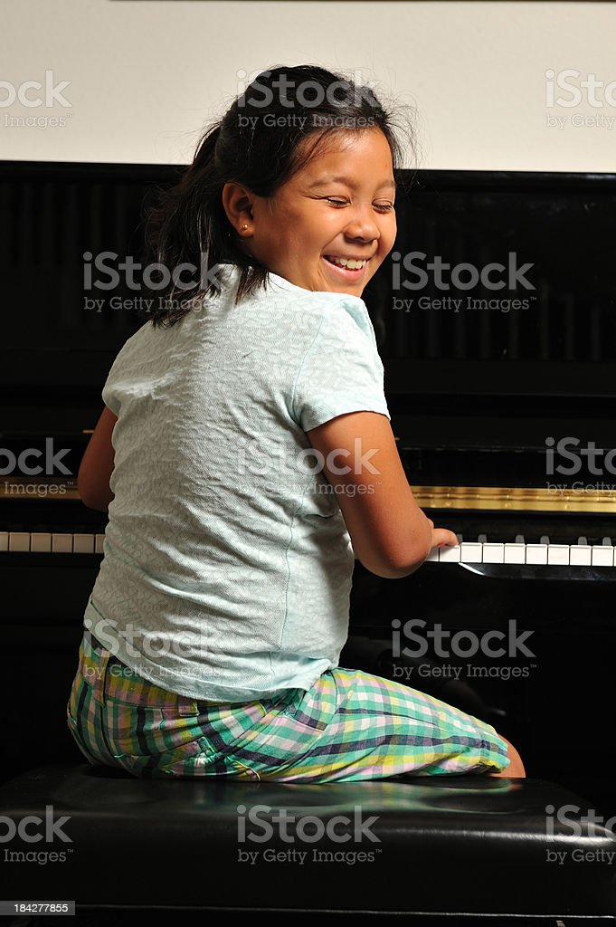 Young girl giggling at the piano royalty-free stock photo