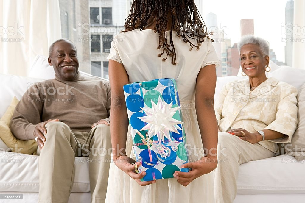 Young girl giving grandparents a gift stock photo