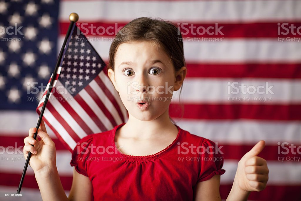 Young Girl Giving Thumbs Up, in Front of American Flag royalty-free stock photo
