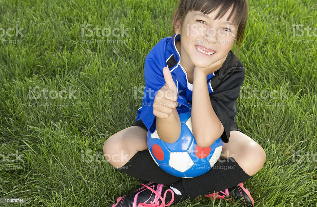 Young girl giving thumbs up on the soccer field royalty-free stock photo