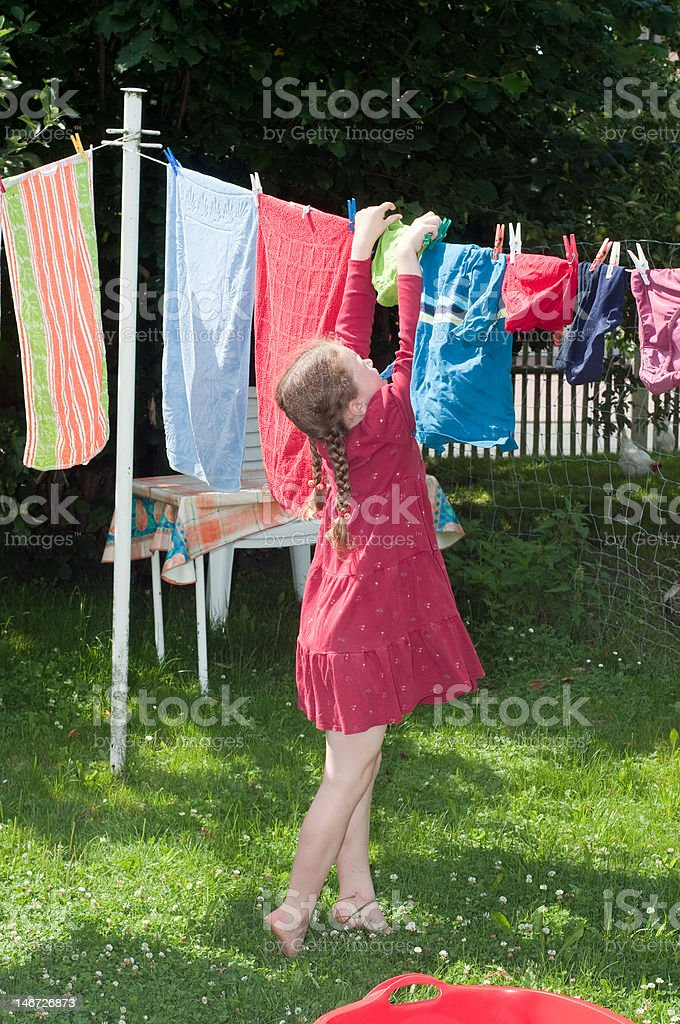 young girl hanging clothes to dry royalty-free stock photo