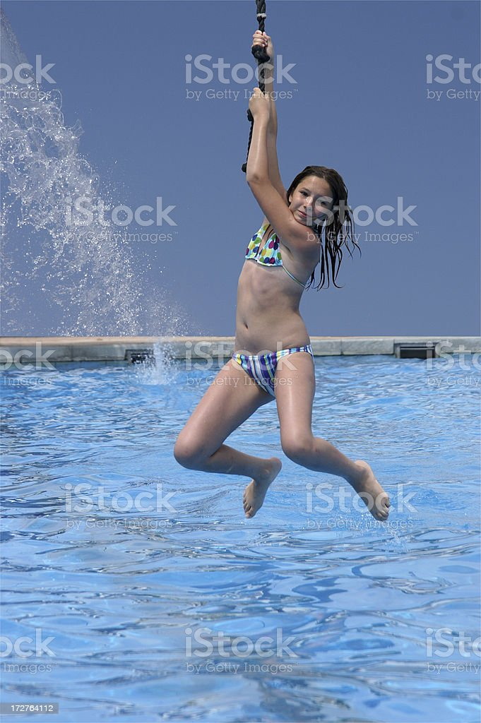 Young girl  hanging on a rope above pool royalty-free stock photo