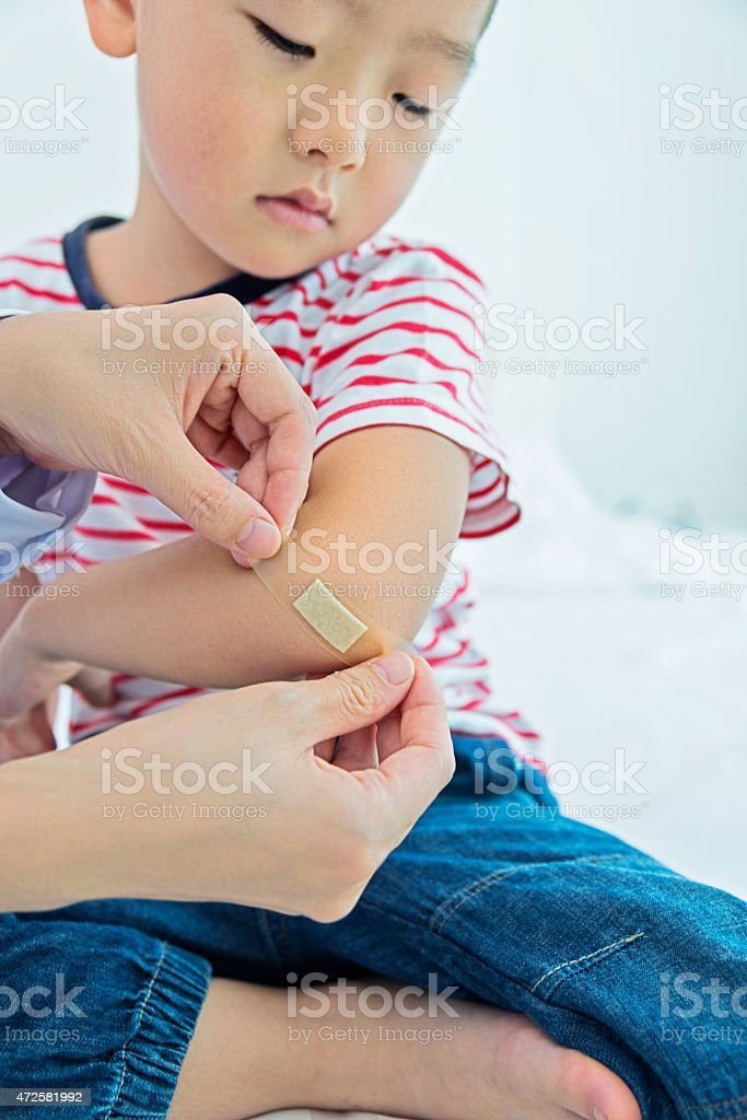 A young girl having a plaster administered stock photo