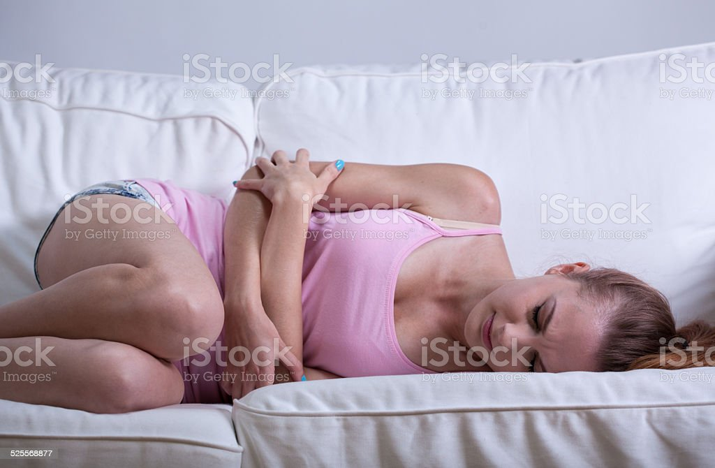 Young girl having abdominal cramps stock photo