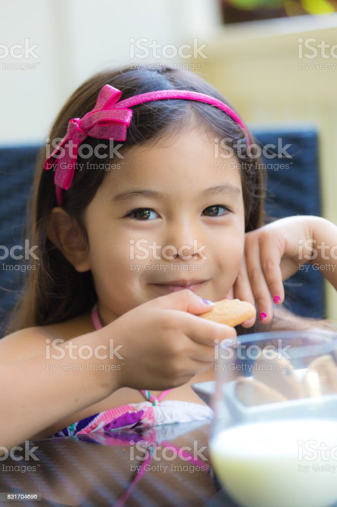 Young girl Hawaiian Polynesian Children with Cookies and Milk stock photo