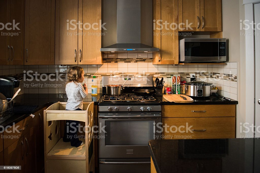 Young girl helps to cook pasta dinner stock photo