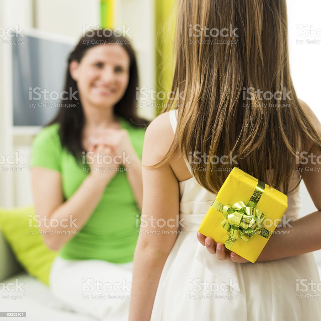 Young girl hiding a present behind her back for her mother stock photo