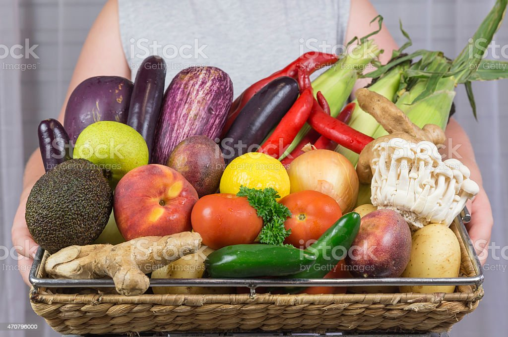 Young Girl Holding a Basket Full of Fruit and Vegetables stock photo