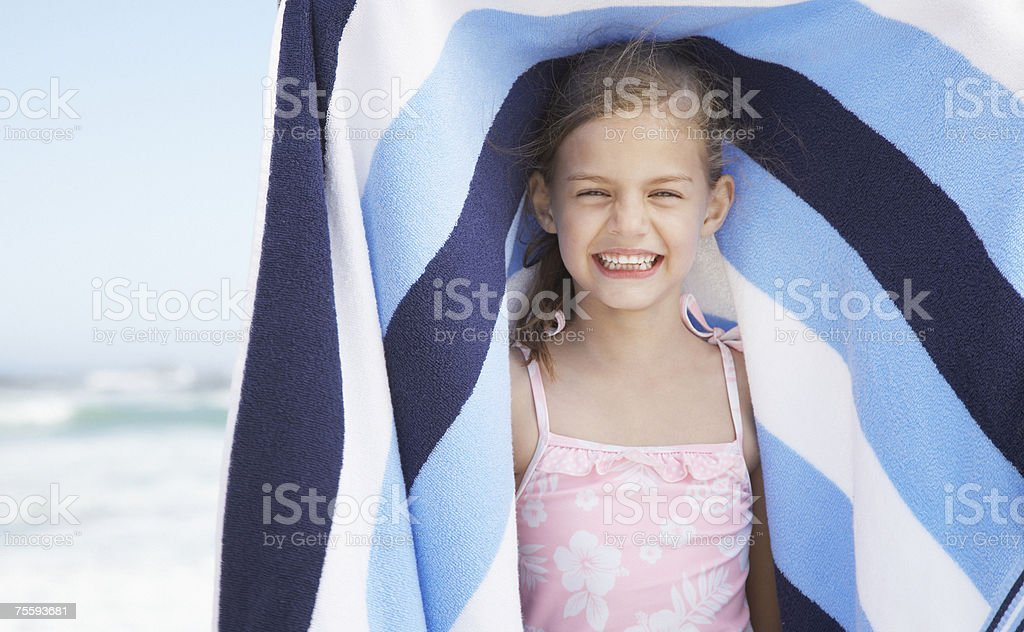 A young girl holding a beach towel royalty-free stock photo