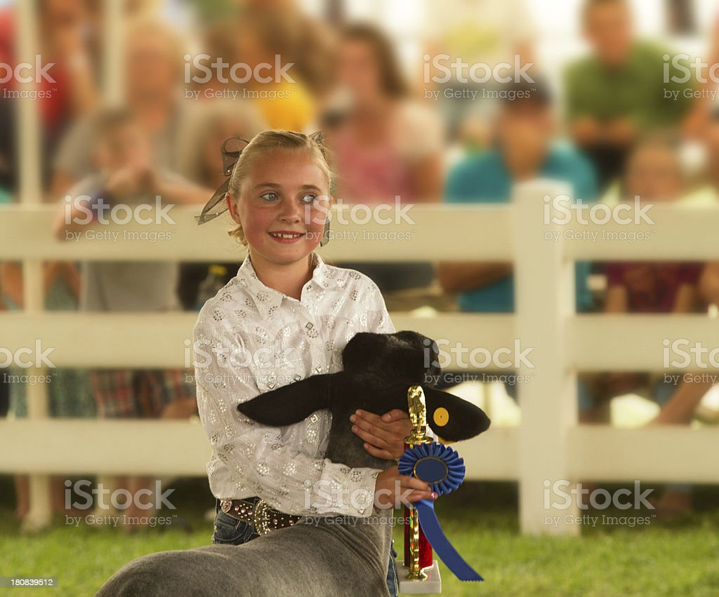 A young girl holding a blue ribbon and a baby cow in a fair royalty-free stock photo