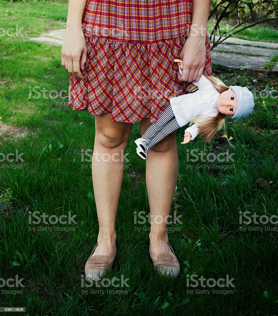 Young girl holding a doll. Leaving childhood stock photo