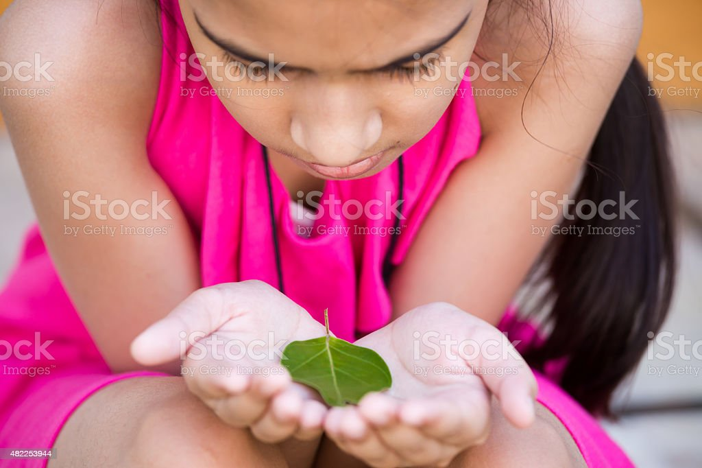 young girl holding a green leaf and thinking about environment stock photo