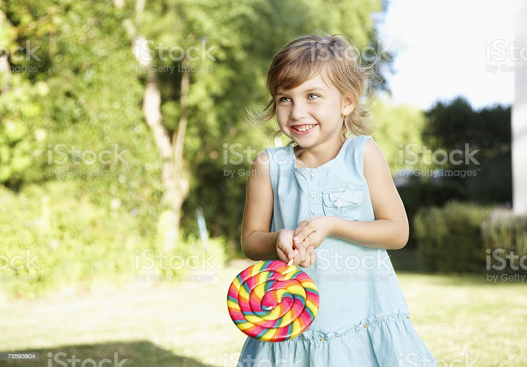 A young girl holding a large lollipop royalty-free stock photo