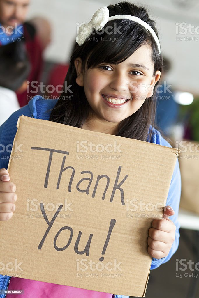 Young girl holding a thank you sign at donation center royalty-free stock photo