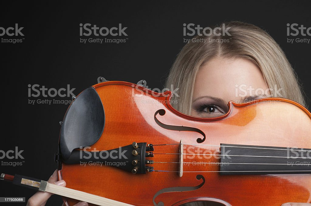 young girl holding a violin and looking through it stock photo