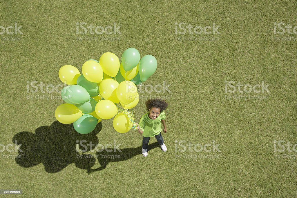 Young girl holding bunch of balloons stock photo