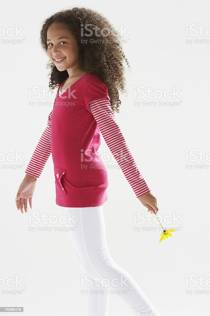 Young girl holding flower indoors royalty-free stock photo