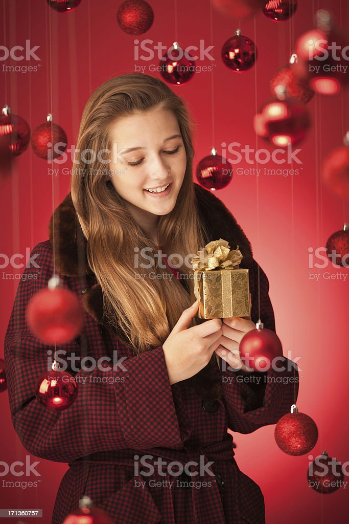 Young Teen girl in winter fashion holding a small gold Christmas gift...