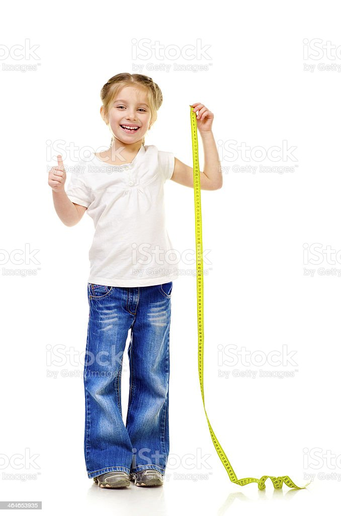 Young girl holding measuring tape celebrating her height royalty-free stock photo