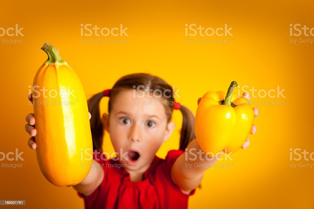 Young Girl Holding Orange Bell Pepper and Squash royalty-free stock photo