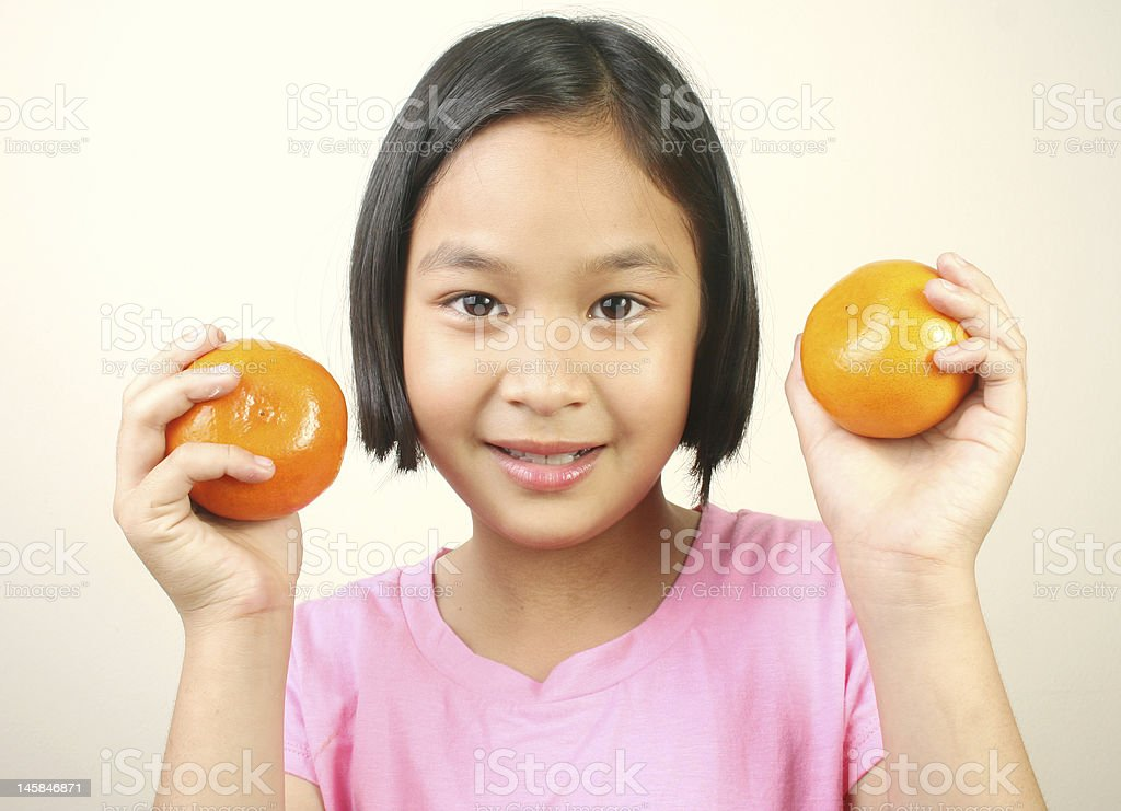 Young girl holding oranges. royalty-free stock photo