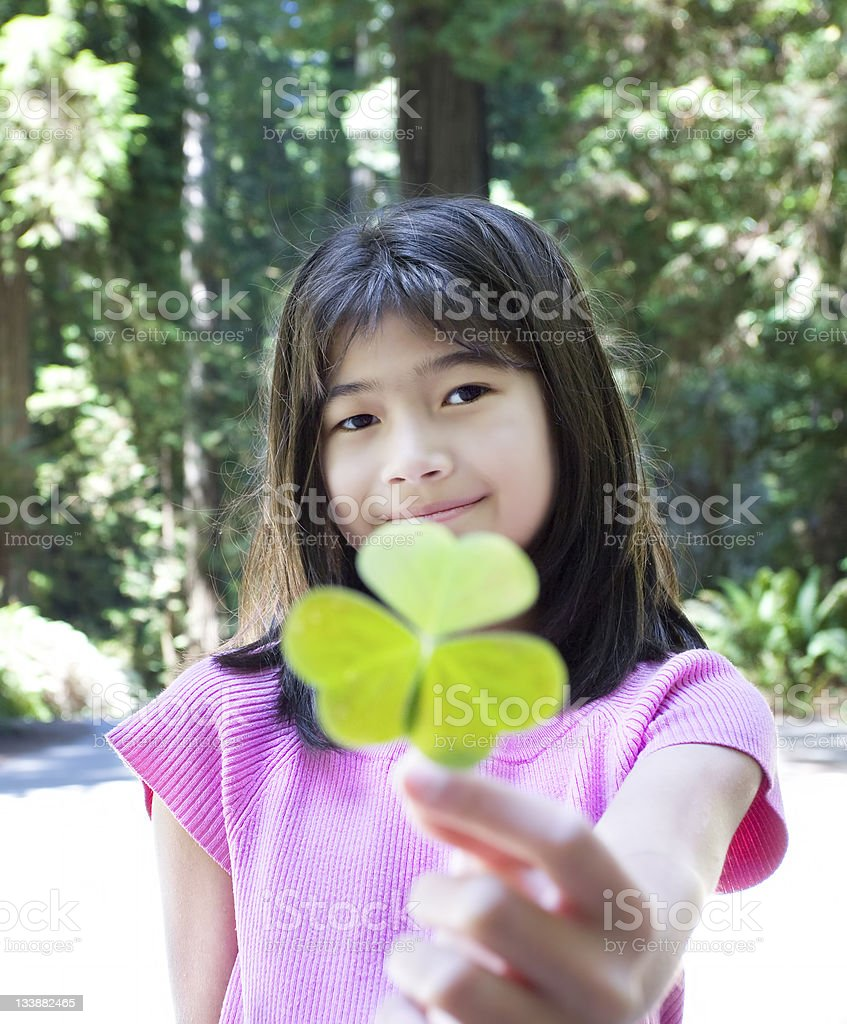 Young girl holding out large three leaf clover stock photo