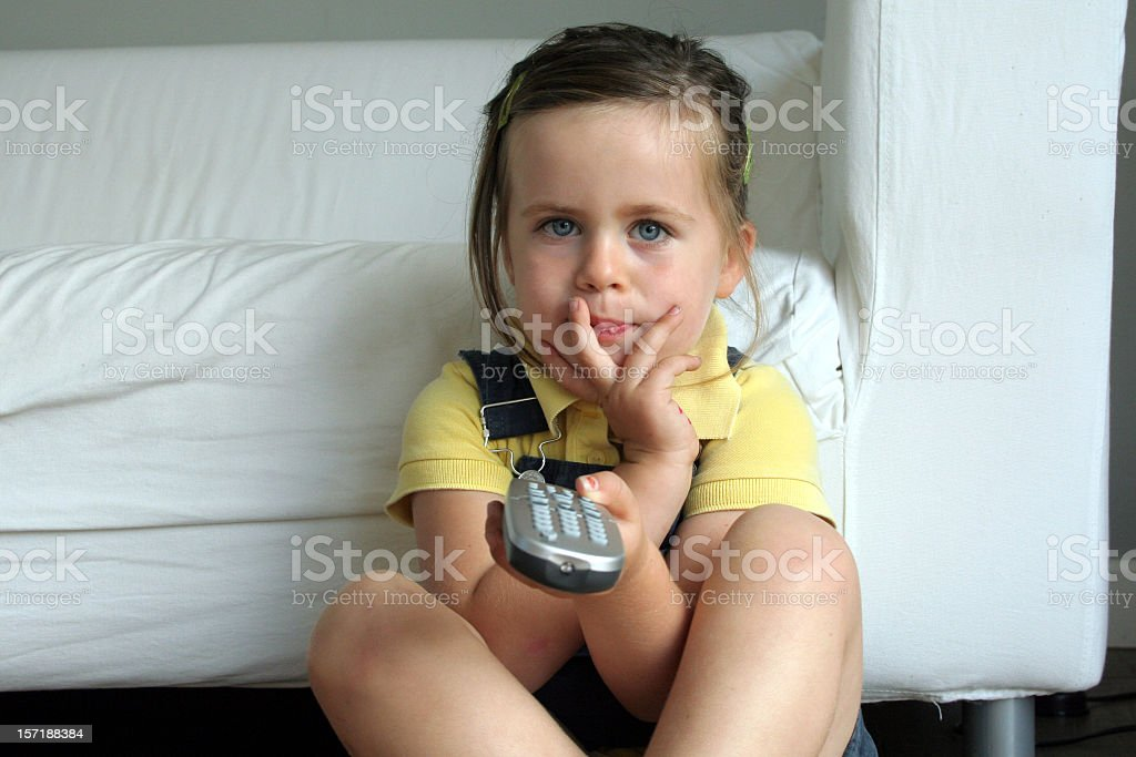 Young girl holding remote and watching television royalty-free stock photo