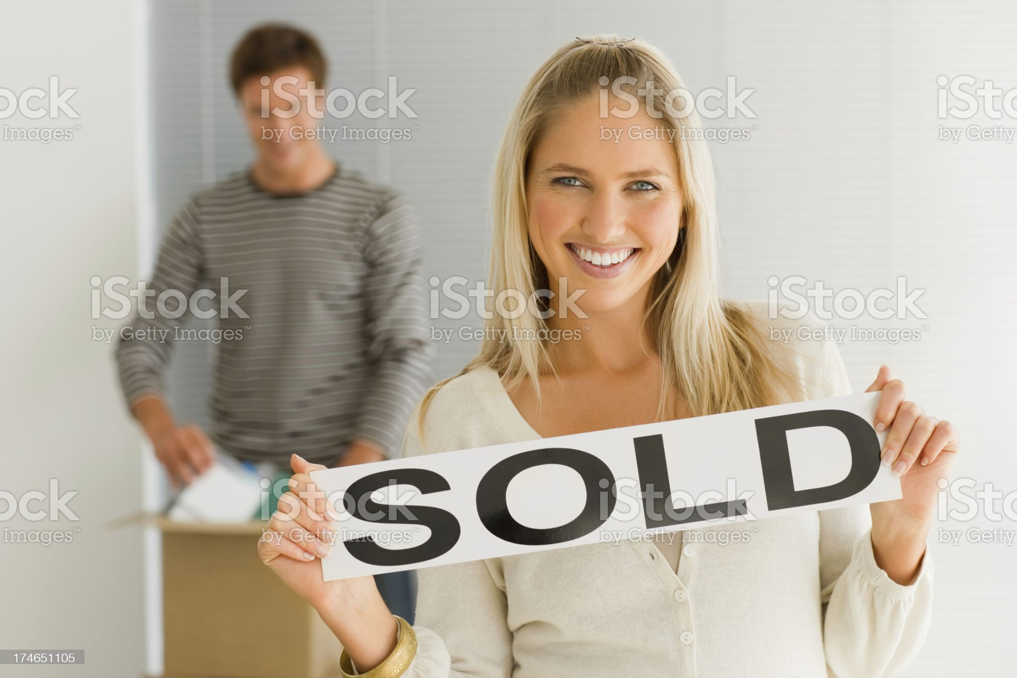 Young girl holding sold placard with man in background royalty-free stock photo