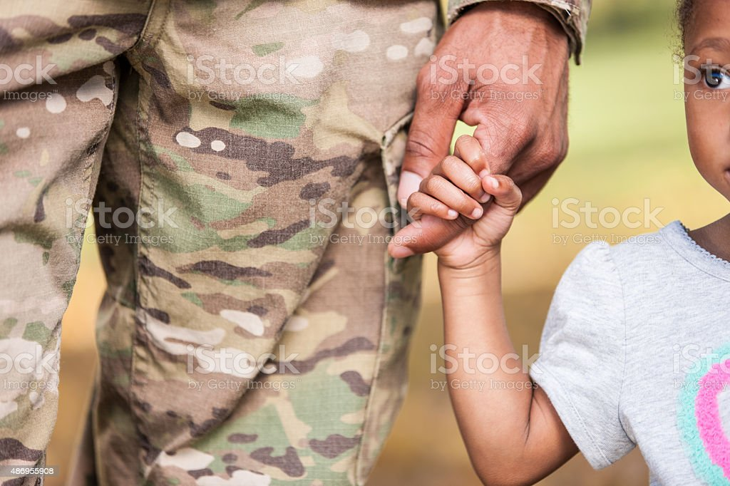 Young Girl Holds Soldier Daddy's Finger stock photo
