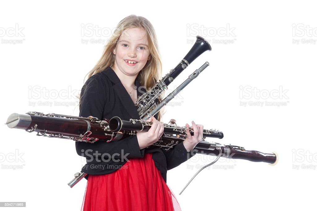 young girl holds woodwind instruments in studio stock photo