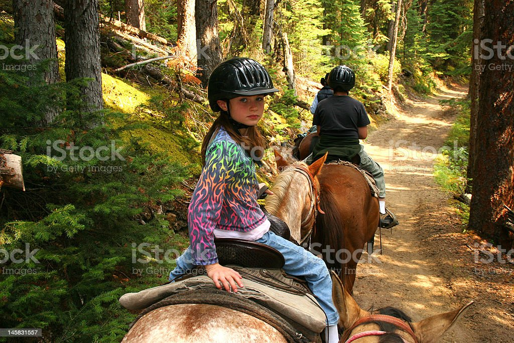 Young girl horse back riding on forest trail. stock photo