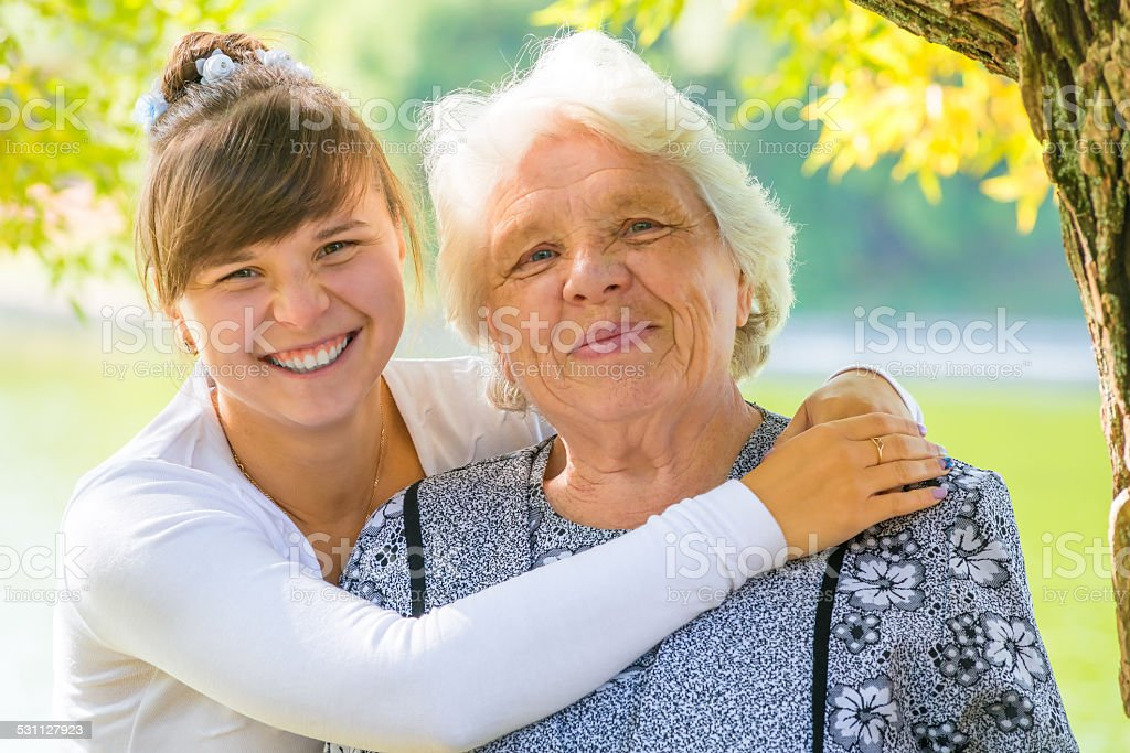 young girl hugging her beloved grandmother stock photo