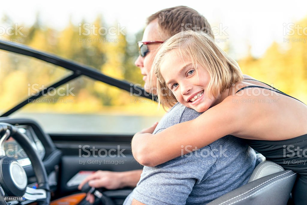 Young girl hugging her father from behind stock photo