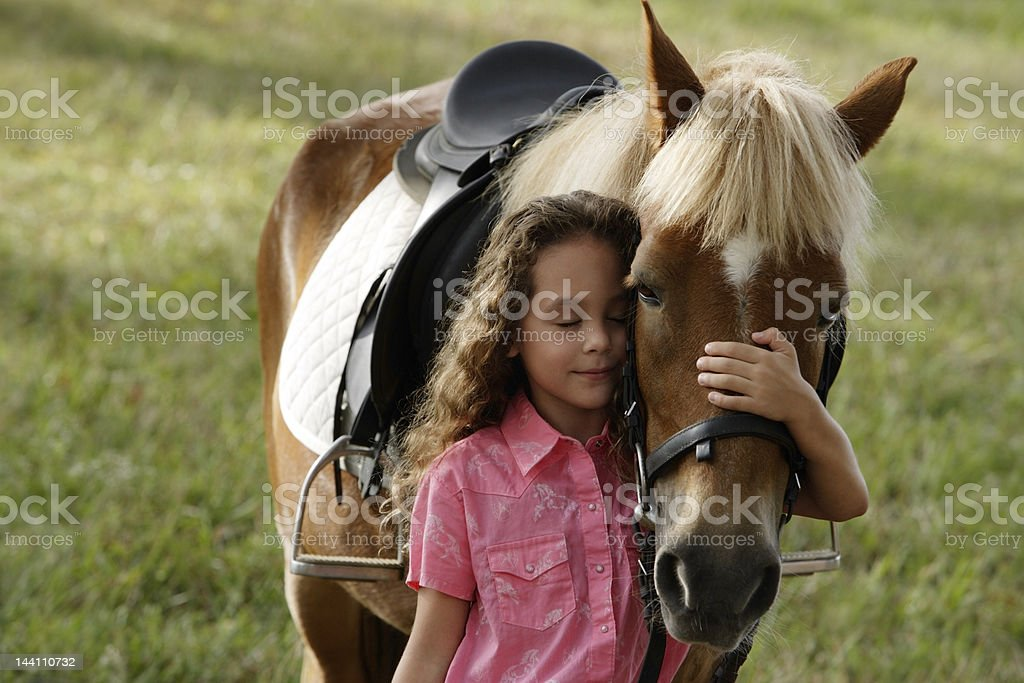 Young girl hugging nose of pony stock photo