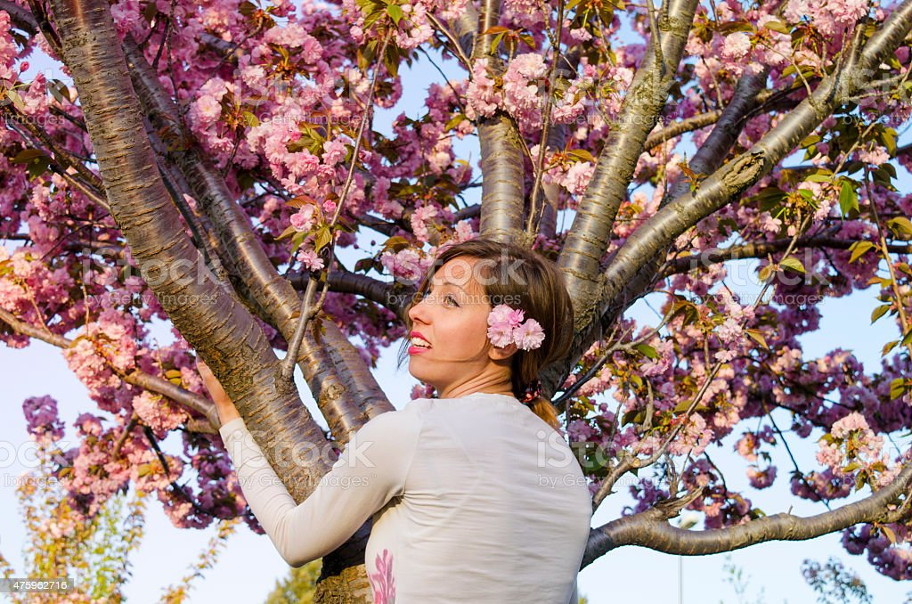 Young girl hugging tree in blossom stock photo