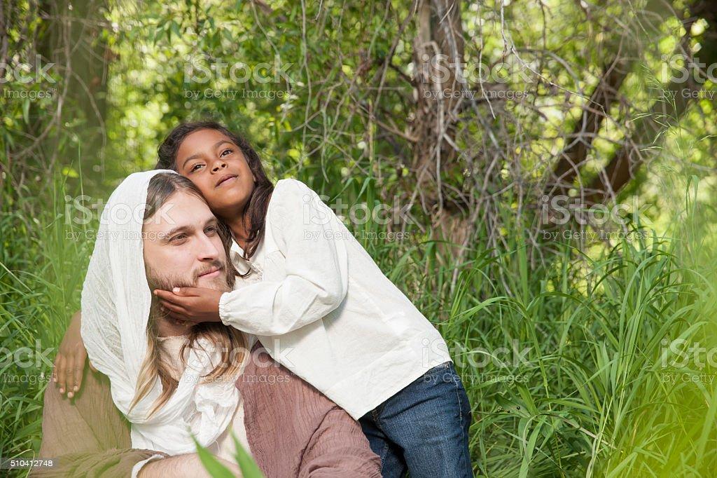 Young Girl Hugs Jesus stock photo