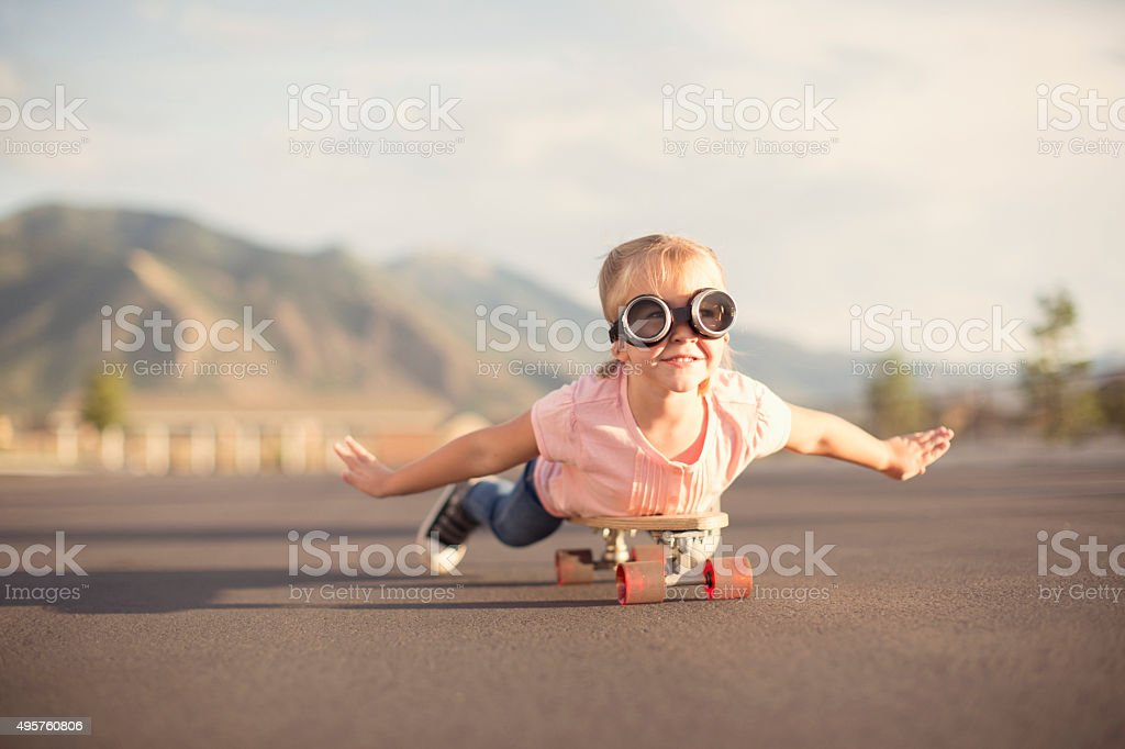 Young Girl Imagines Flying On Skateboard stock photo