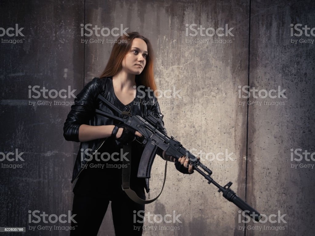 young girl in a black leather jacket with a gun machine. Luxurious long red hair. stock photo