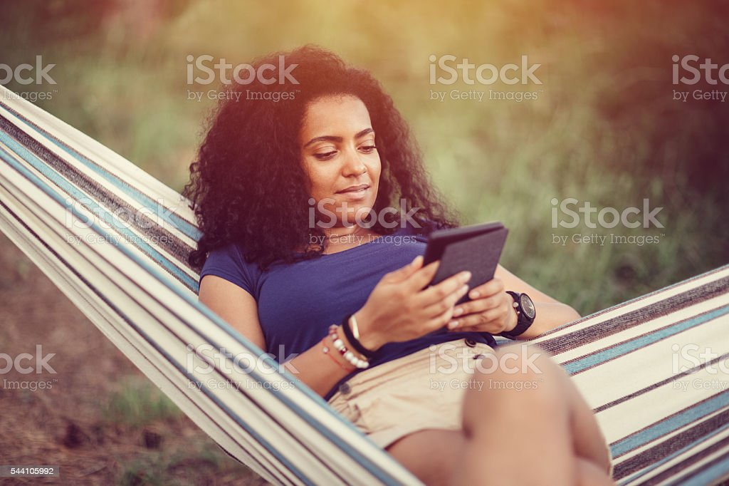 Young girl in a hammock with e-book stock photo