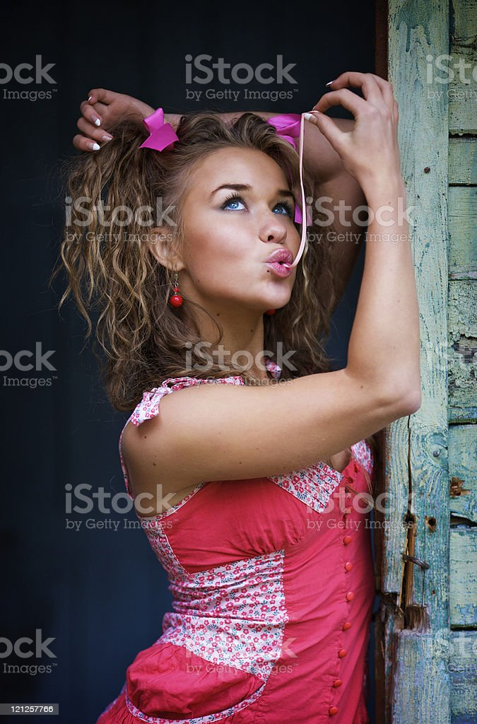 Young girl in a pink dress eating chewing gum royalty-free stock photo