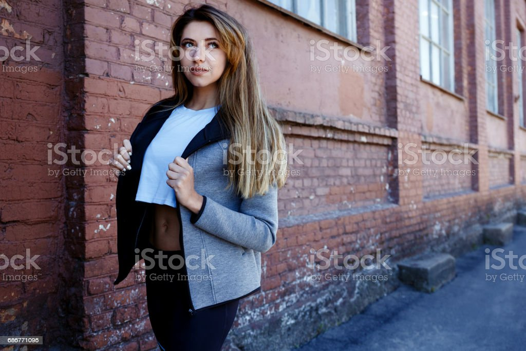 Young girl in a sportwear is exercising in front of the urban red brick wall. Phot was made on a sunny morning. stock photo