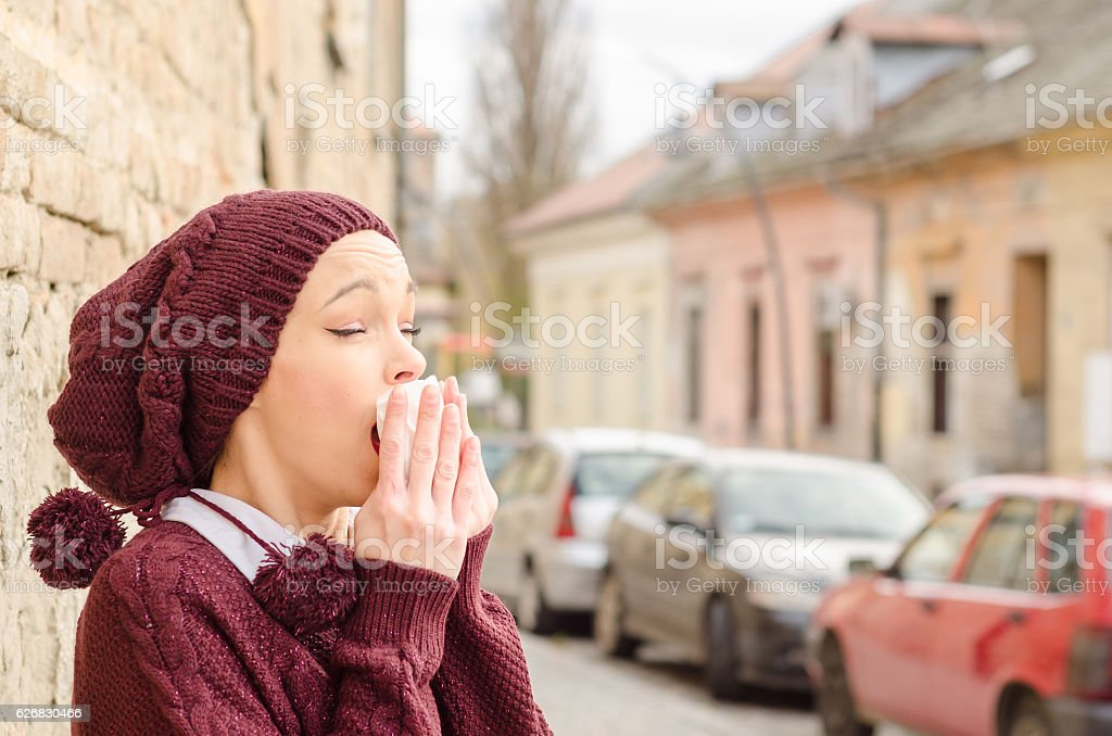 young girl in a sweater standing on the cold weather stock photo