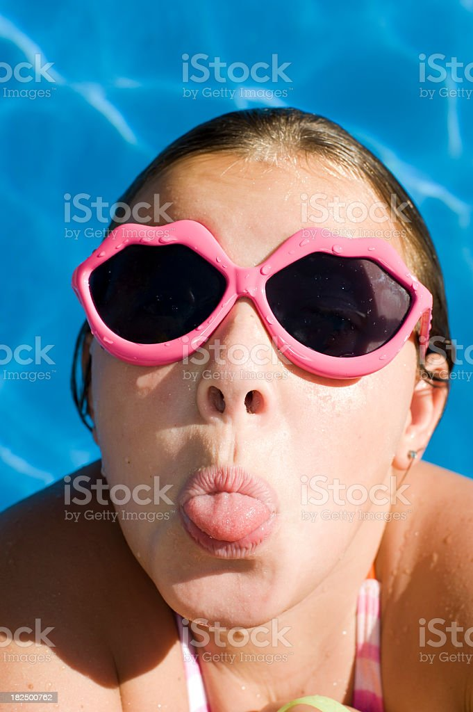 Young girl in a swimming pool poking stock photo