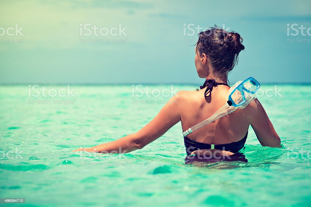 young girl in a tropical sea with a mask for snorkeling stock photo