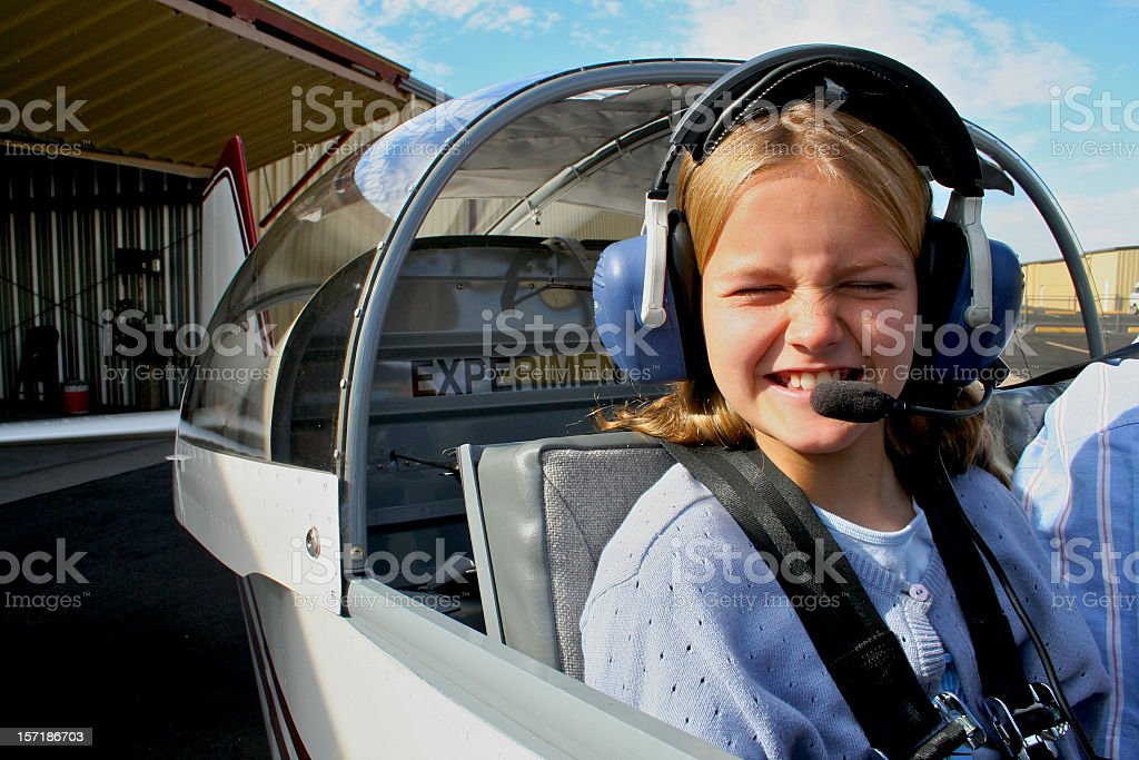 Young girl in an airplane, ready to fly stock photo