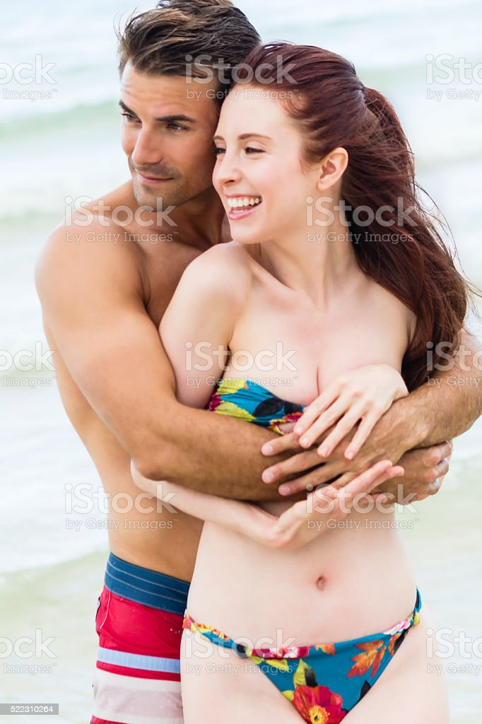 Young girl in bikini smiles being hugged by young man stock photo