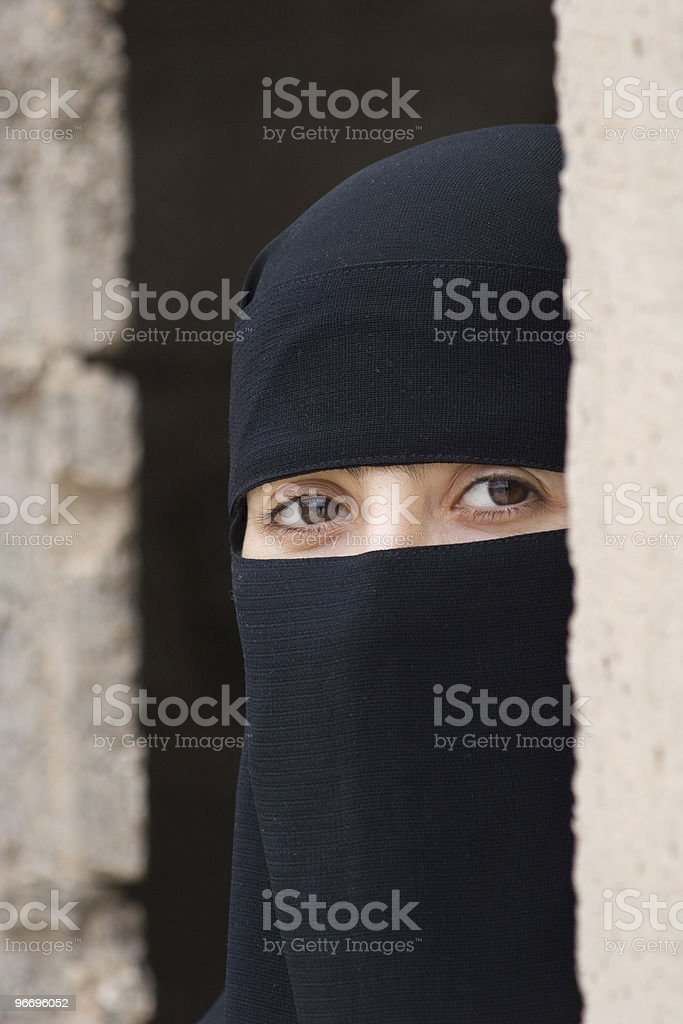 Young Girl In Black Veil Looking Behind Wall royalty-free stock photo