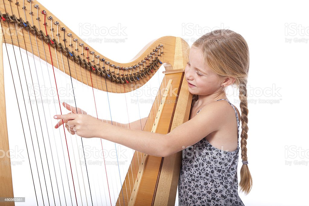 young girl in blue playing harp stock photo