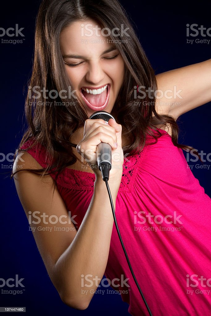 Young girl in bright pink top singing into microphone royalty-free stock photo