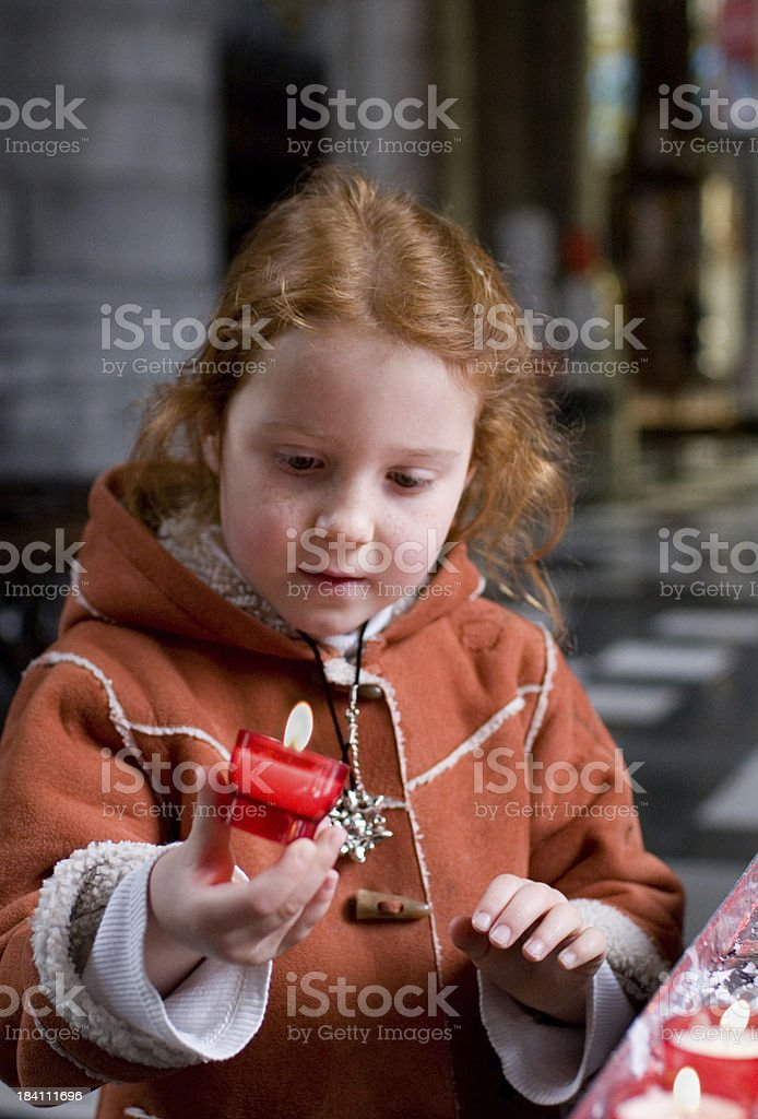 Young girl in church, holding a candle royalty-free stock photo